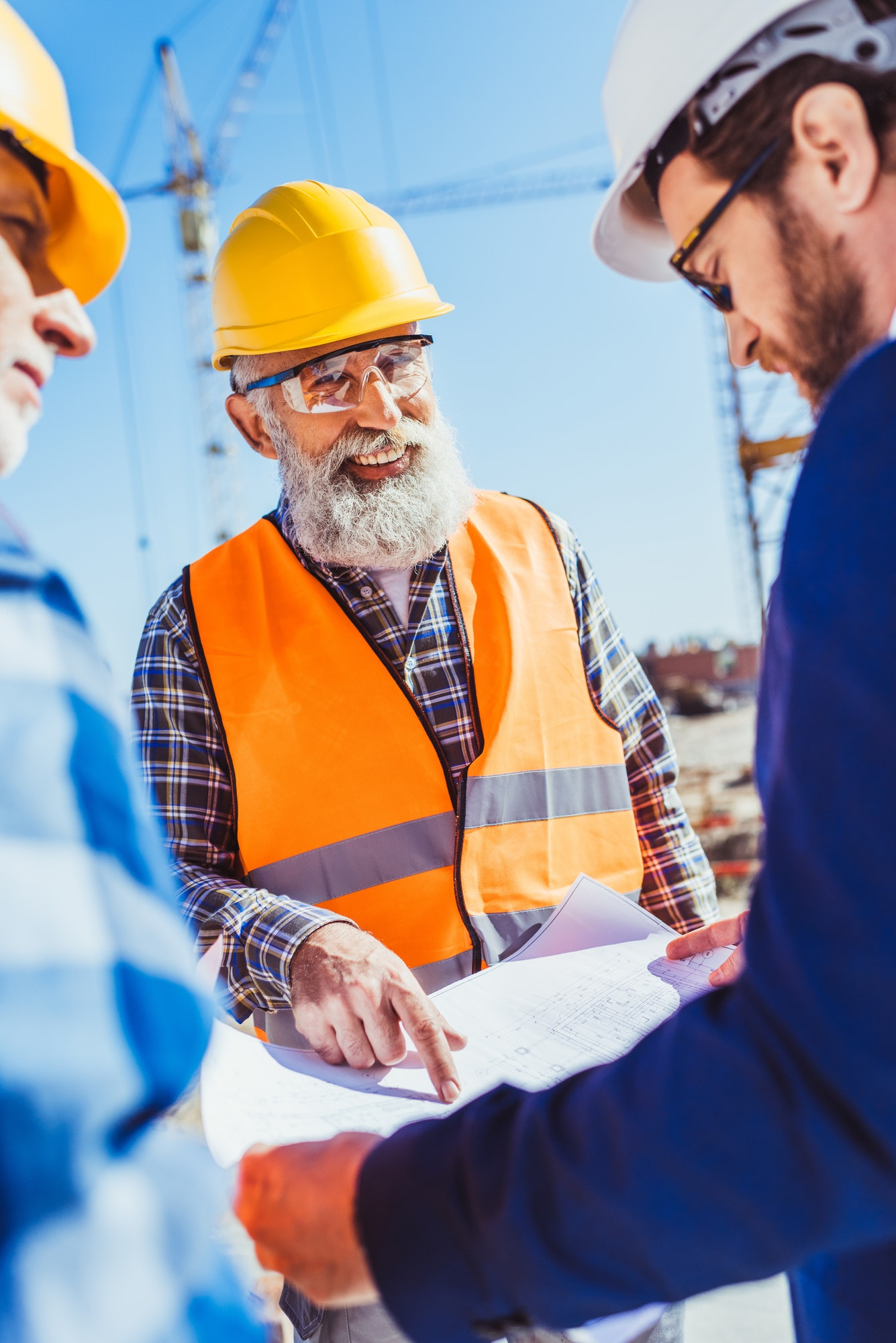 Construction worker in protective uniform discussing building plans with businessman in hardhat and