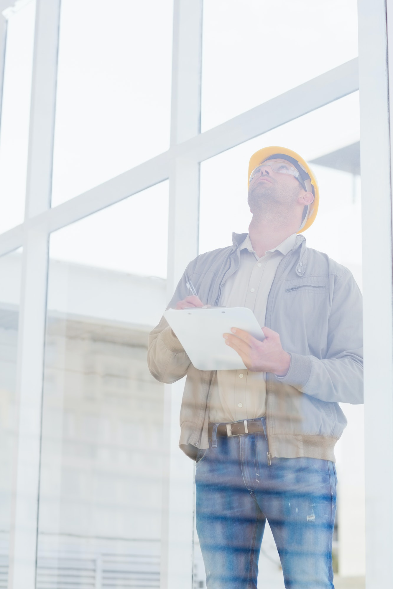 Male supervisor looking up while writing on clipboard in office